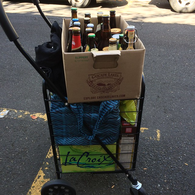 The beer is, yes, precariously perched upon the top of the full cart. It's a more careful perching than it looks.