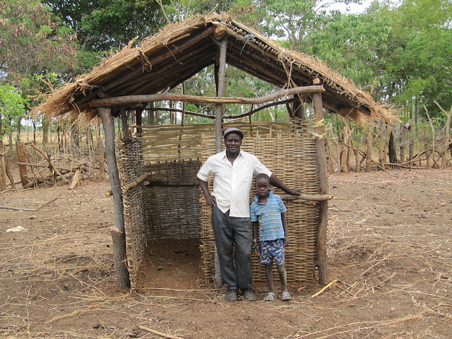 A farmer and his son stand in fromn tof their new manure collection structure. Photo credit: Sebastian Scott