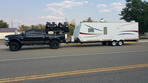 A Dodge Ram Hauling Atvs On The Bed Pulls A Camper Flickr