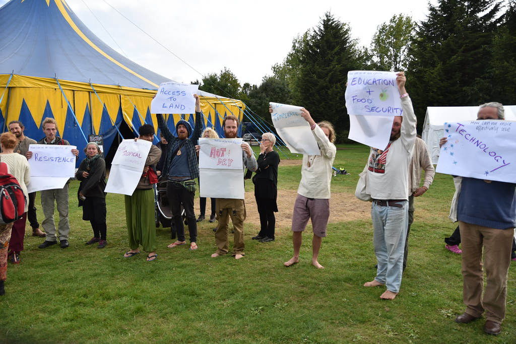 "Permaculture practitioners hold up topic signs to create thematic working groups.  Signs visible include ""Technology"" ""Education and food security"" ""Hot dry climates"" ""Access to land"" and ""Resistance"""