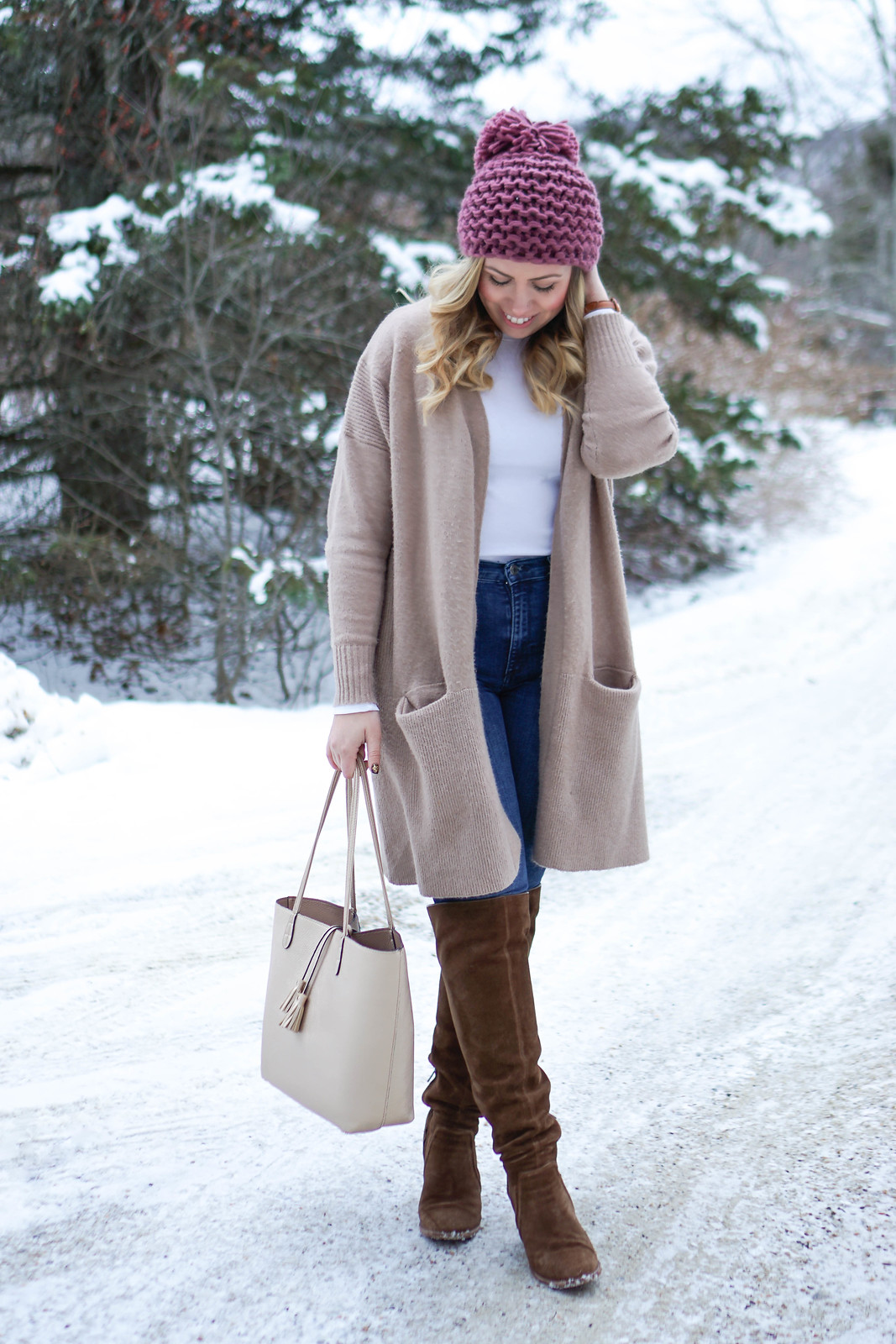 Casual Winter Pastel Outfit in Snow | Pink Pom Pom Beanie and Camel Oversized Sweater Gap High Waisted Jeans Vince Camuto OTK Brown Suede Boots