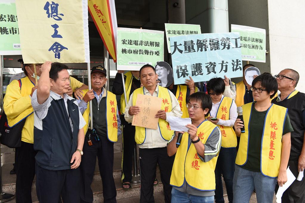 桃市府勞動局勞資關係科長馮飛燿(左一)出面接受陳情時,對於宏達電是否違反《大解法》問題,表示仍有待行政認定。(攝影:宋小海)