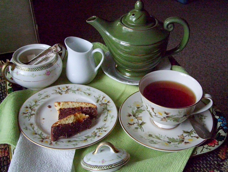 tea tray with pot, cup and saucer, plate with biscotti