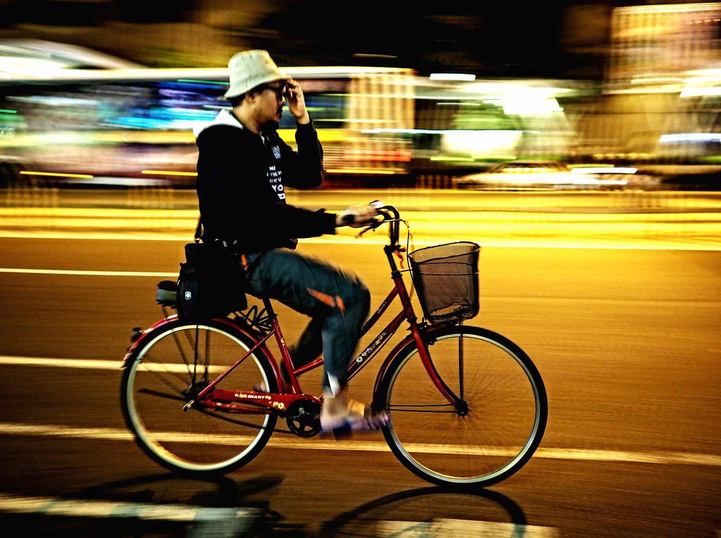 A hat-wearing cyclist whizzing along Roosevelt Road in Taipei