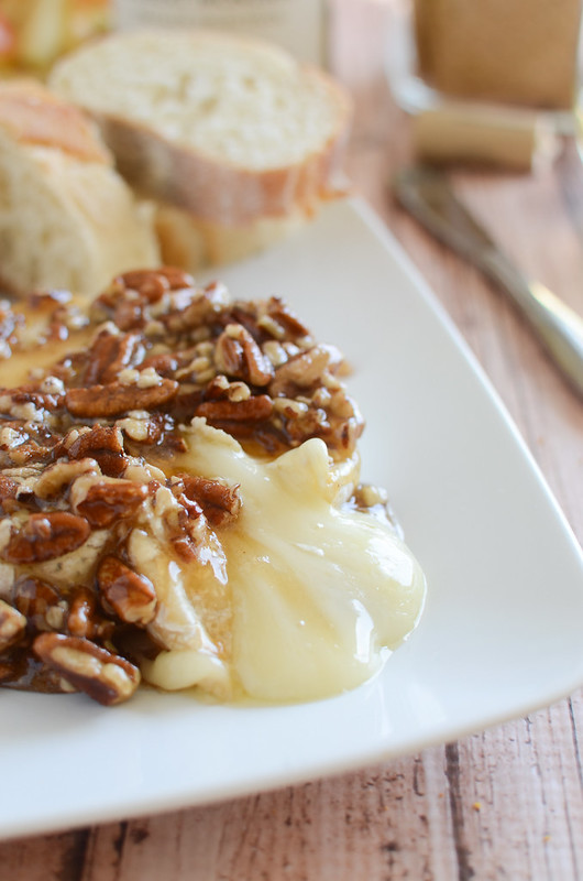 Maple Pecan Baked Brie - delicious melty brie topped with a maple, brown sugar, and pecan mixture. Serve with apple slices and graham crackers! Perfect holiday appetizer!