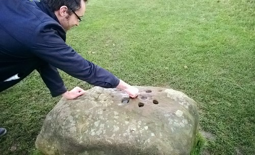 visitor places a coin on Eyam's boundary stone