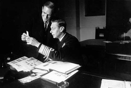 King George VI looks through stamps