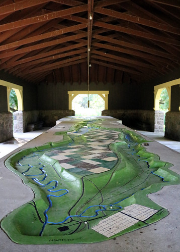 mostly green relief map with a painted blue river flowing through it, under exposed beams of a large, open building