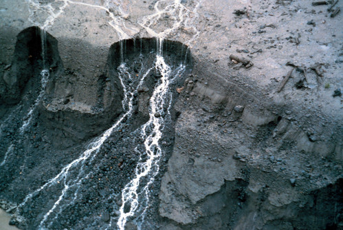 Image shows a cliff of volcanic debris. A braided stream has cut two waterfalls into them, and is eroding the edges back in circular patterns.