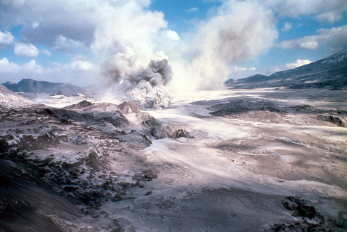 Image shows pale tan and white volcanic deposits filling the North Fork Toutle River valley. There are a few ridges and hummocks visible, with the slope of Mount St. Helens peeking from the upper right. In the distance, ash and steam rise from the valley floor in a chaotic plume, merging with a blue sky dotted with fluffy white clouds.