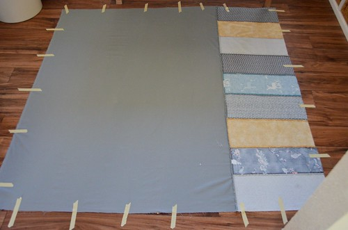 "1. Mark center of edges of quilt backing with safety pins and tape to floor with masking tape. Use ""parachuting"" method to ensure it lays flat."