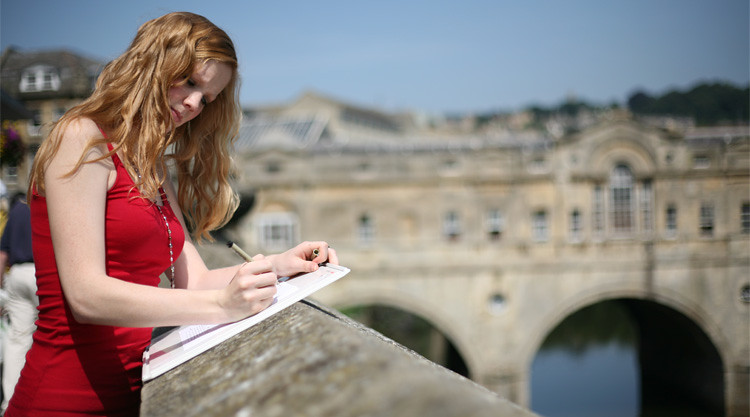 Student sketching on paper with Pulteney Bridge in Bath behind her