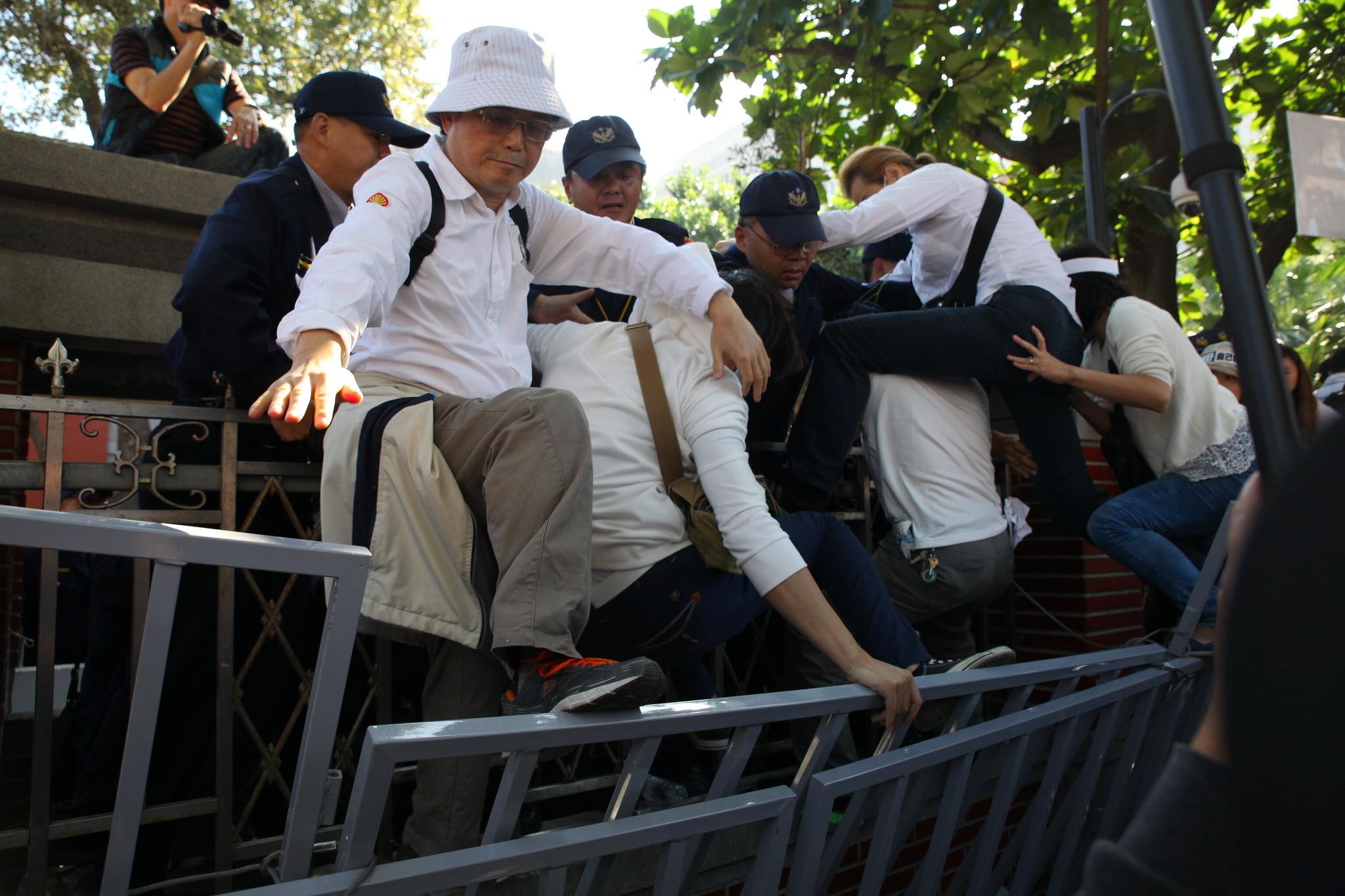 反同婚方試圖攀爬立院圍牆,與警方發生衝突,舞台主持人要求警方「釋放公民」不要阻擋。(攝影:陳逸婷)