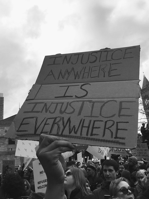 "A handmade protest sign, which reads ""Injustice anywhere is injustice everywhere"""