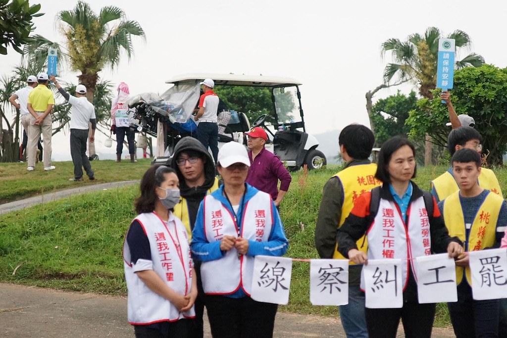 選手(左上方)在罷工封鎖線一旁擊球,有球場員工對工會高舉「請保持安靜」告示。(攝影:王顥中)