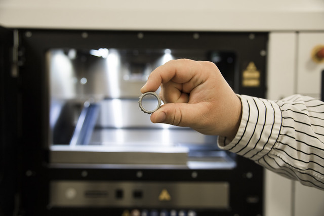 A person's hand is seen holding a small metal ring in front of a 3-D printer.
