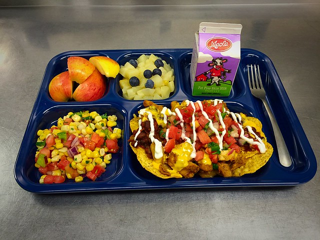 A tray with fruits, vegetables, milk and nachos