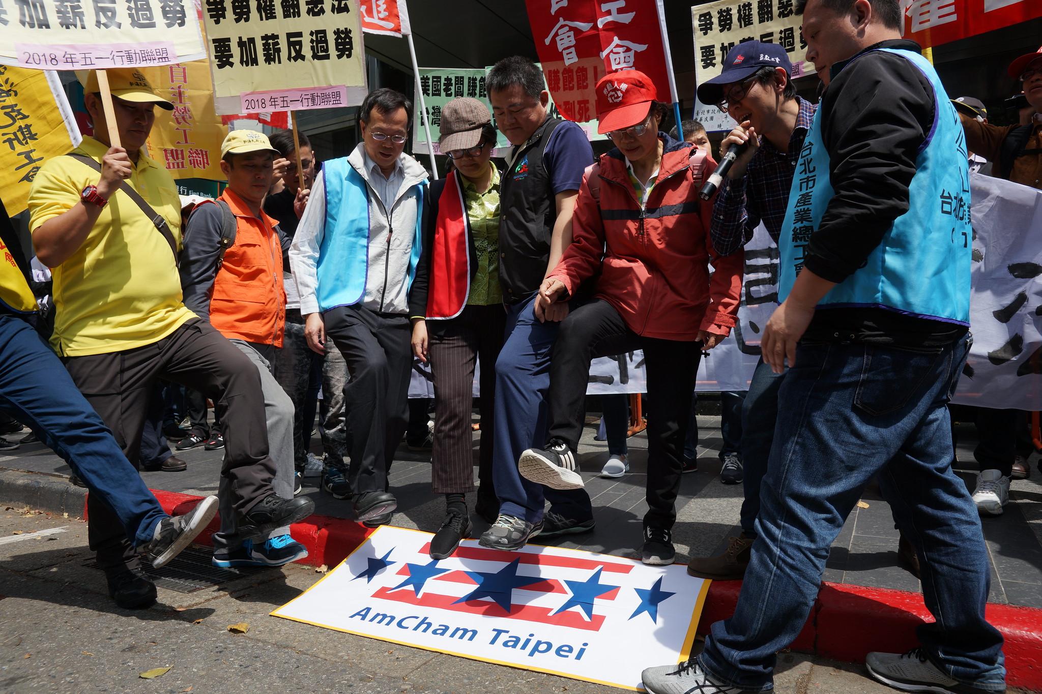 勞團踩破寫有台北美國商會(AmCham Taipei)字樣的看板。(攝影:王顥中)