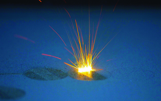 A spark is seen during the additive manufacturing process.