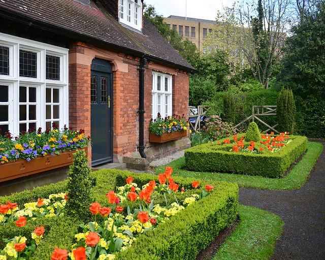 Casita junto a jardín repleto de flores con ventanas blancas de madera