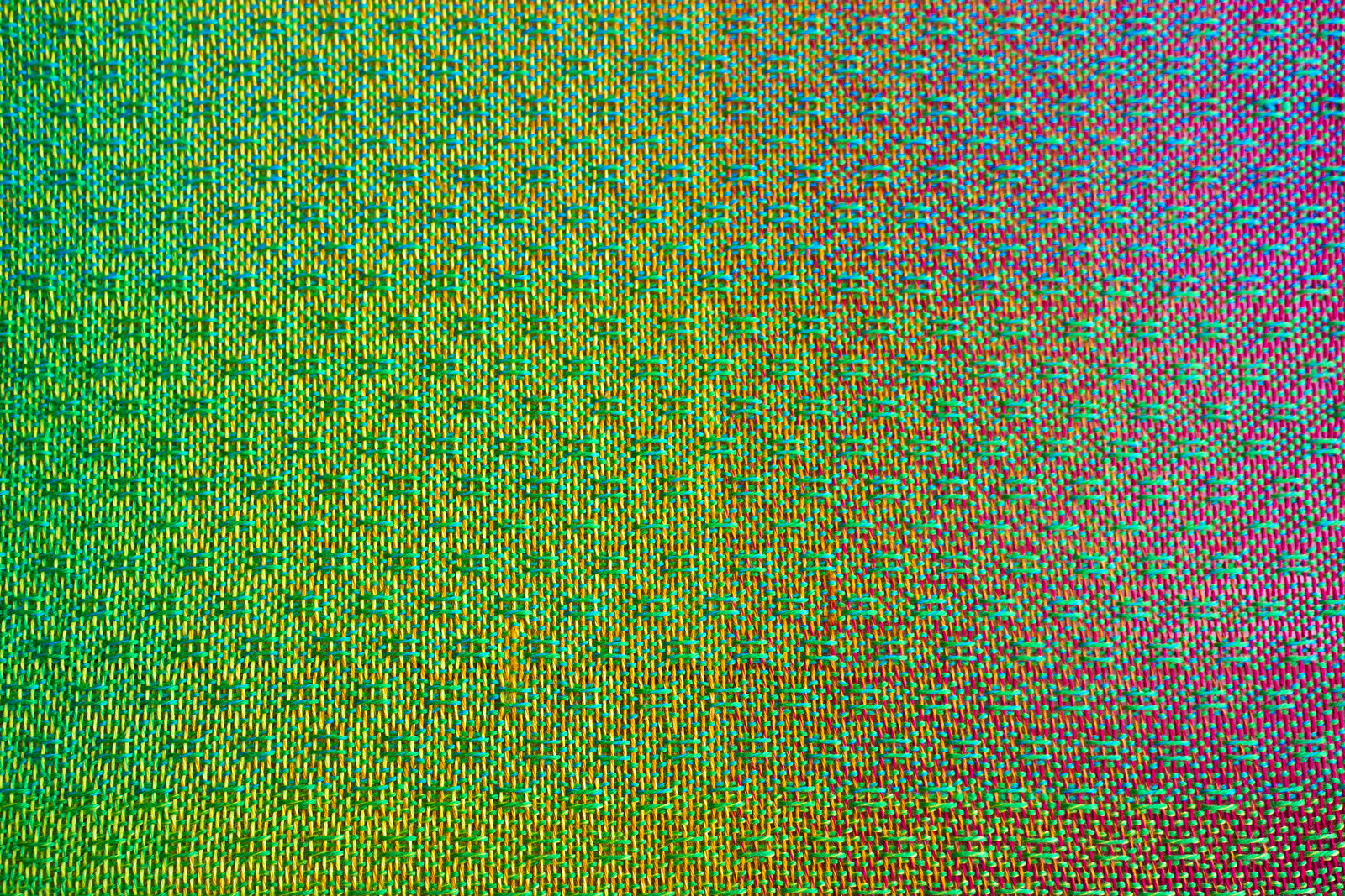woven cloth in a mixture of colours, primarily green, woven in spot bronson pattern
