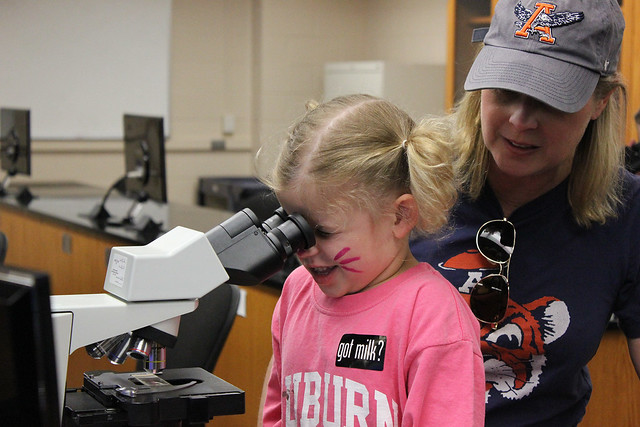 A young girl looking through a microscope.
