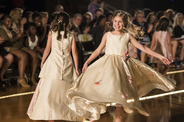 Two little girls in white dresses walk down the runway.