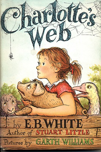 "Book cover of ""Charlotte's Web"" by E. B. White: A girl with a short pony tail holds a pig in her arms, while a goose and a sheep stand next to her, looking up at her expectantly"