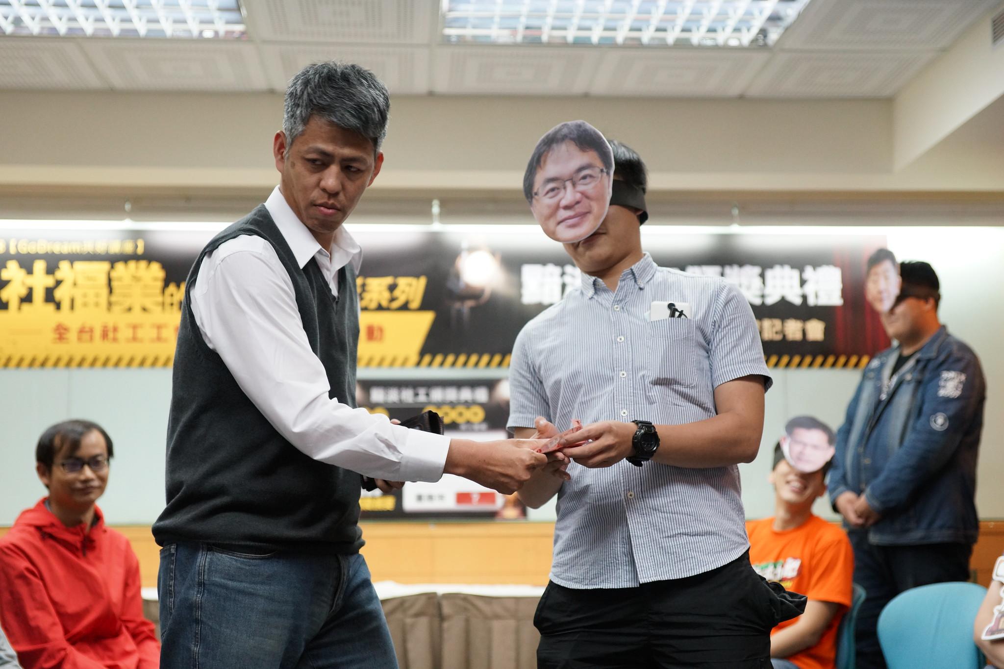 頒獎典禮上,工會成員扮演台南市代理市長李孟諺(右),接下社工從皮夾掏出的鈔票,諷刺台南市社工被要求回捐薪資的狀況嚴重。(攝影:王顥中)