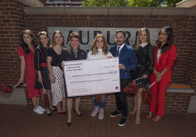 Melissa McCarthy and other movie stars present a check to the president of the Auburn University Foundation.