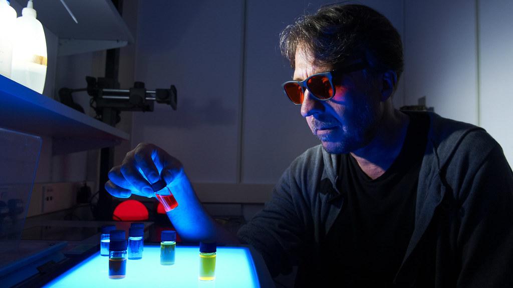 Jean Van Der Elsen in the darkroom with samples glowing under ultraviolet light.