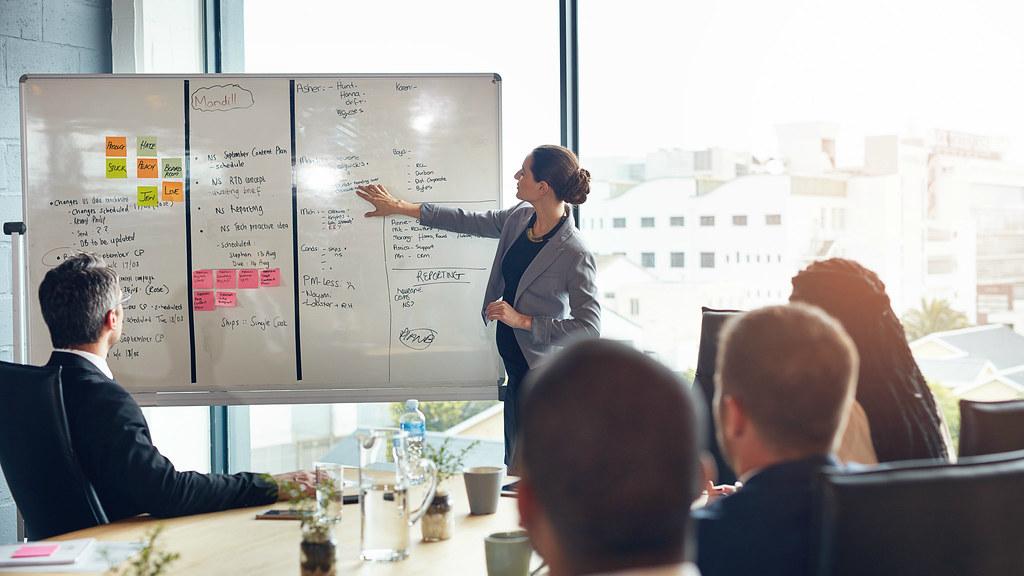 Female presenting in a boardroom