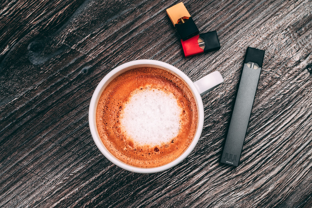 JUUL Podmod Near A Coffee Cup And Some Pods