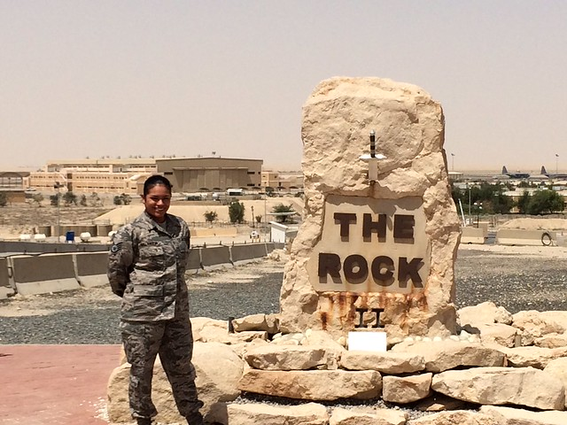 Melissa Villanueva is pictured next to a large rock while deployed overseas in the military