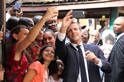 French president Emmanuel Macron poses for selfies during a visit to Louis Pasteur French high school on July 4, 2018, in Lagos.(Getty) | by Al-Majalla