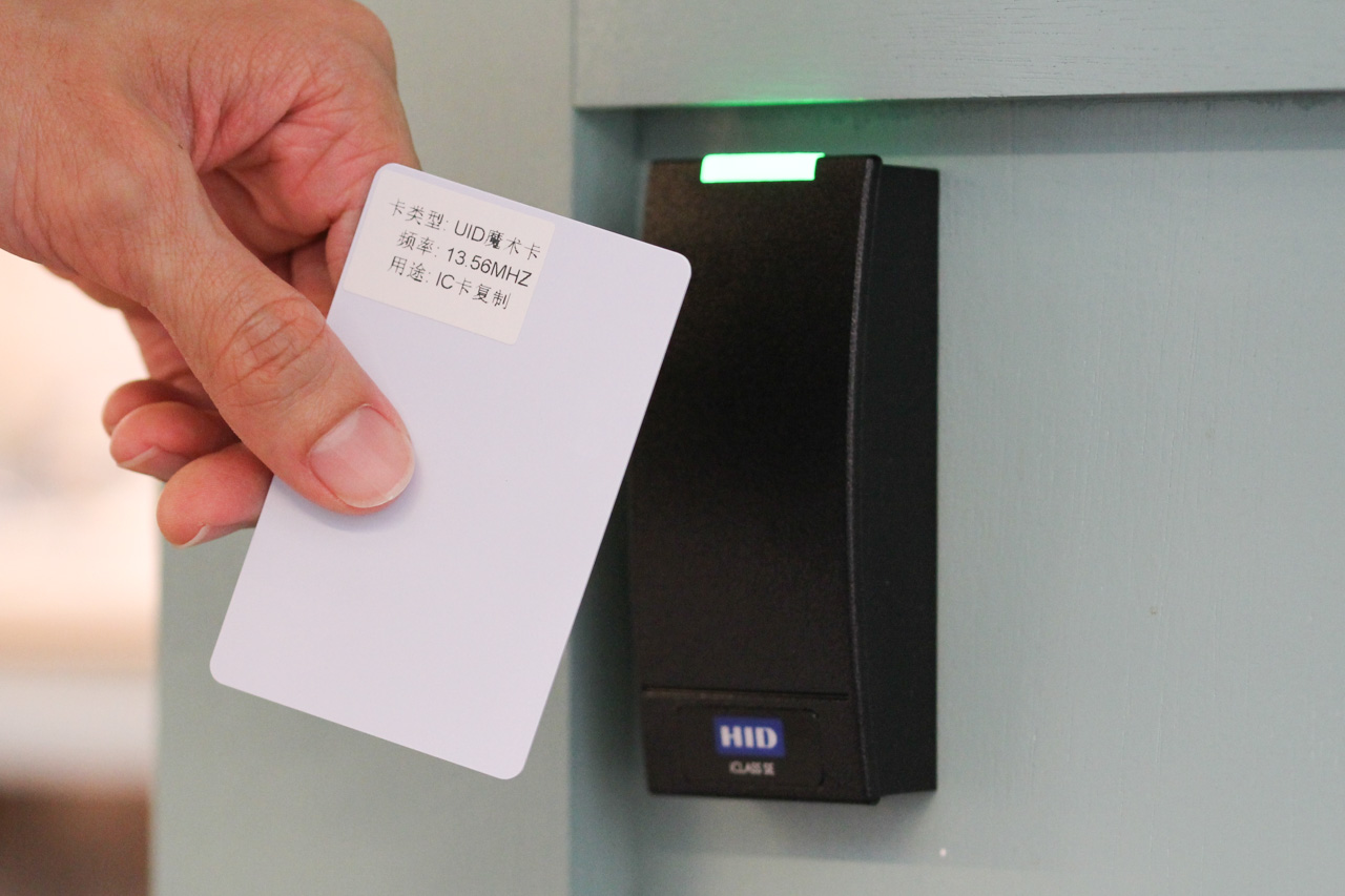a labeled UID 'magic card' held in front of a HID iClass door reader, which turned green to indicate 'access granted'