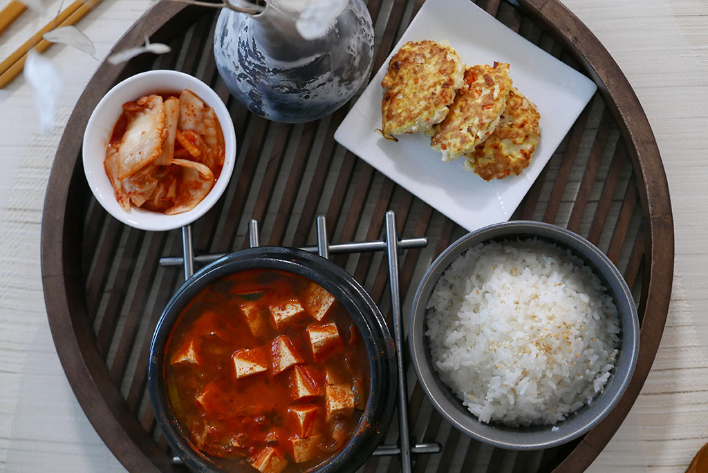 Korean breakfast with doenjang jjigae (soybean paste stew), kimchi, egg and tofu pancakes, and a bowl of rice