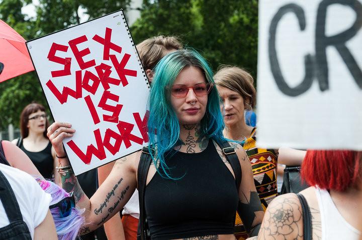 """性工作者手持""""性工作也是工作""""的标语,近日于英国国会前抗议,反对禁止性交易网站的提案。(图片来源:BARCROFT MEDIA VIA GETTY IMAGES)"""