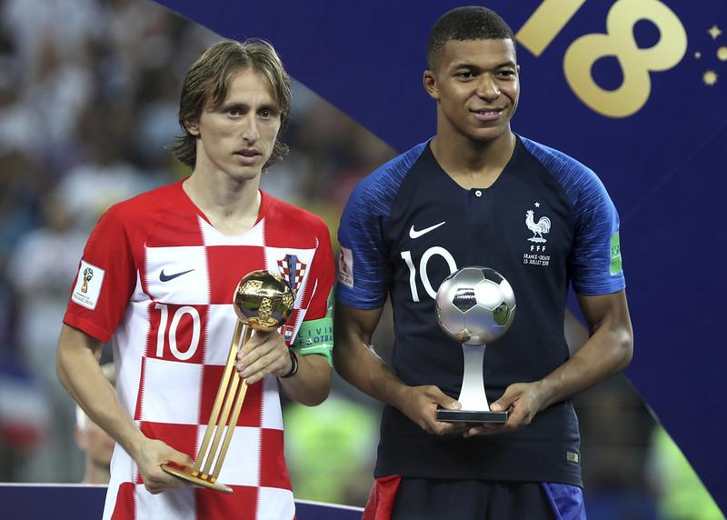 金球獎得主Luke Mordric(左)和最佳年輕球員Kylian Mbappe在頒獎台上合照。(達志影像)