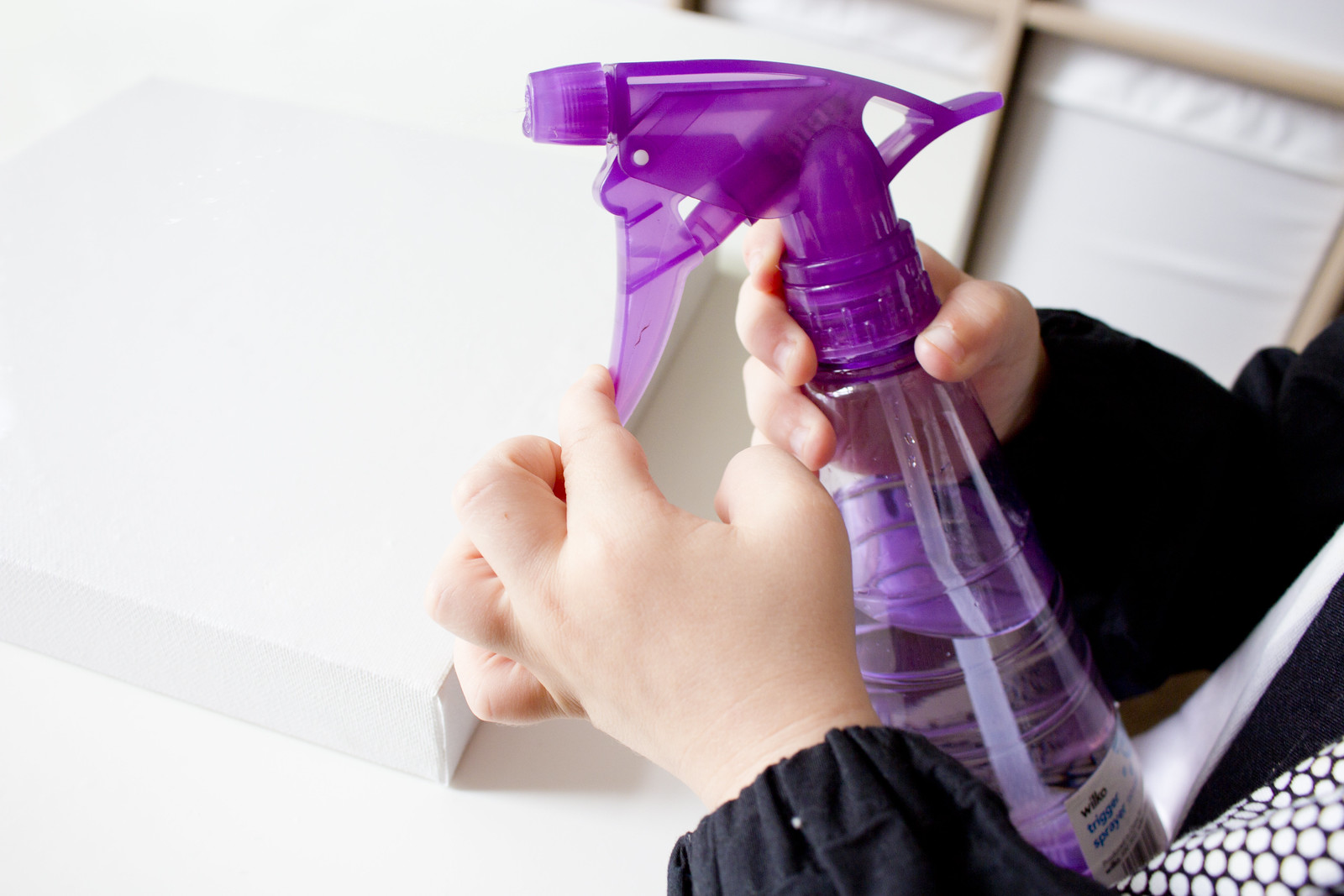 toddler hands holding trigger spray bottle