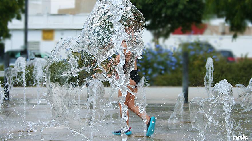 niña jugando en las fuentes de la ciudad en verano