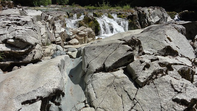 Image shows a partially-eroded basalt dyke cutting through blocks of diorite. A glimpse of the falls is visible beyond.
