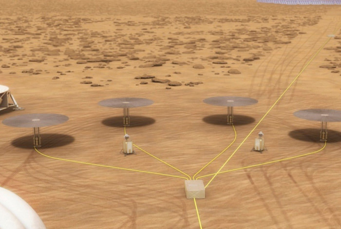 four Kilopower nuclear reactors casting shadows on the Martian surface.