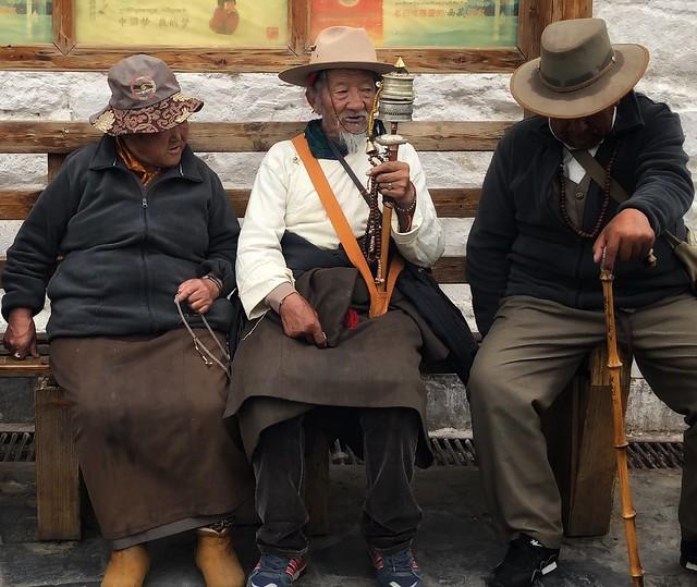 Paisanos tibetanos sentados en un banco