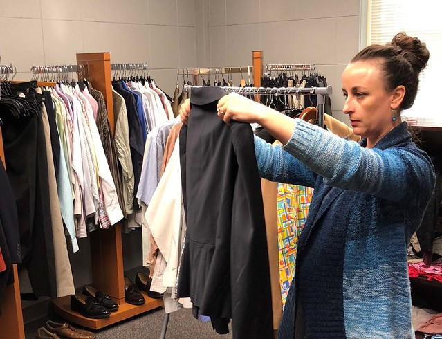 A student looks at a jacket in the Career Closet.