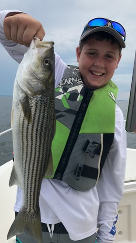 Photo of boy holding a nice striped bass