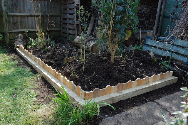 Wooden border round a raised bed