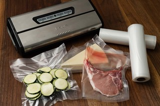 vacuum sealer with food sealed on wooden table and rolls of plastic for sealing | by yourbestdigs