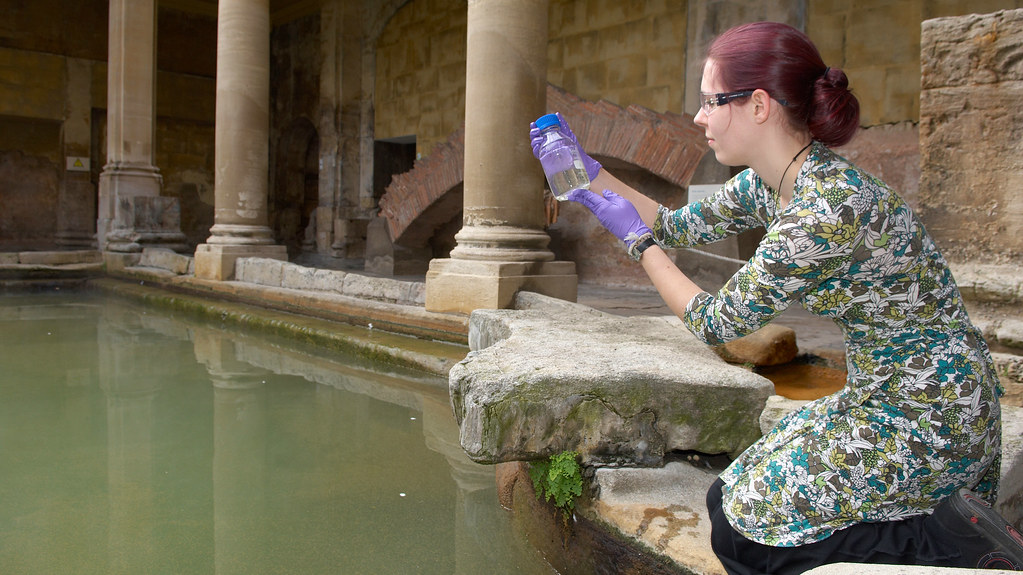 PhD researcher Holly Smith-Baedorf collecting algae samples from the Roman Baths.