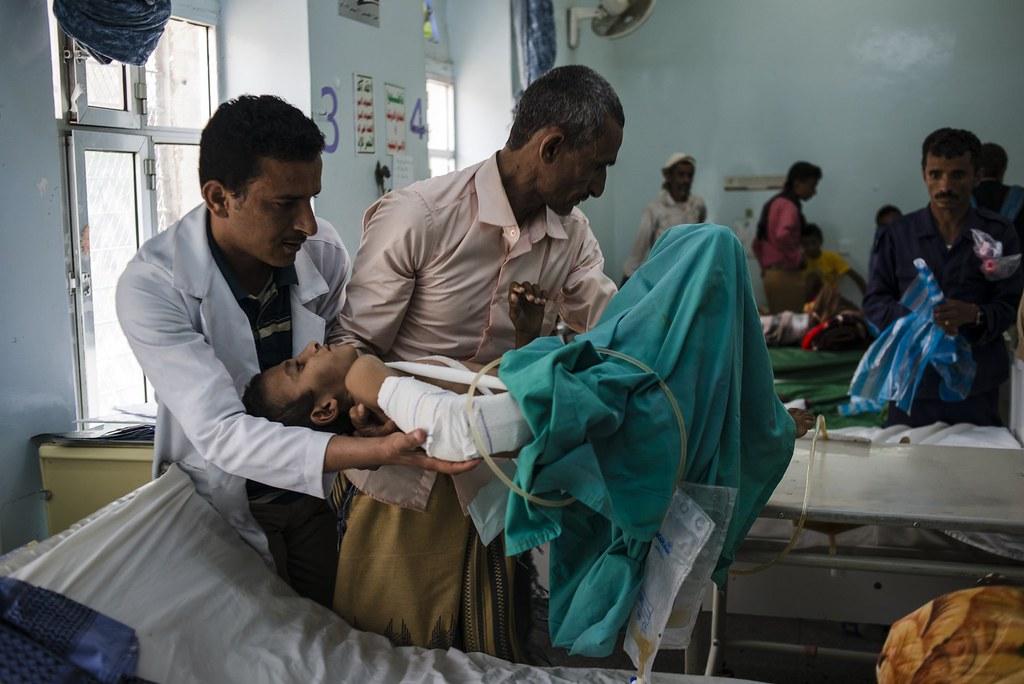 叶门医院中,一名父亲抱起失去一条腿的孩子。(图片来源:Alex Potter for The Intercept)